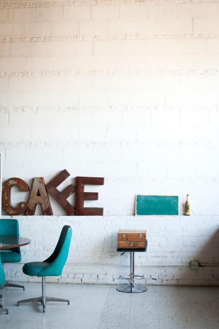 lettre-murale-mur-en-briques-blanches-et-chaises-turquoises