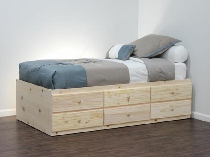 lit-coffre-en-bois-clair-sol-en-parquet-foncé-mur-en-bleu-clair-linge-de-lit-gris-bleu