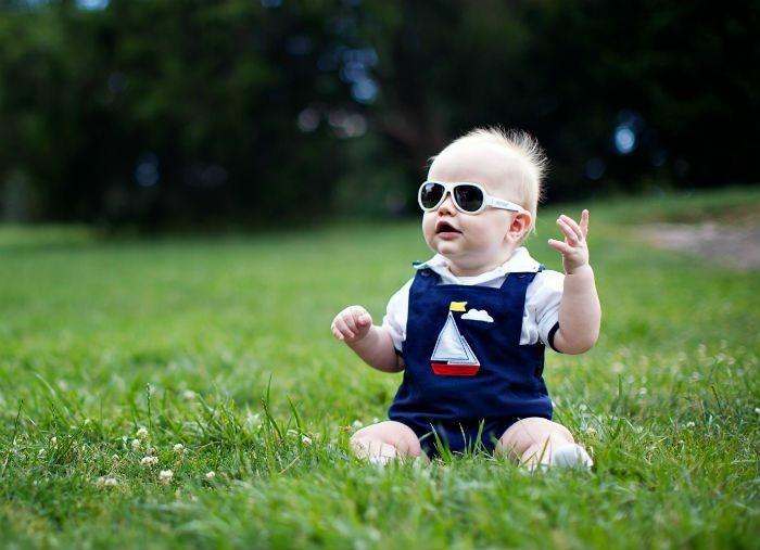 lunettes-soleil-enfant-petit-bebe-assis-sur-l'-herbe-verte-resized