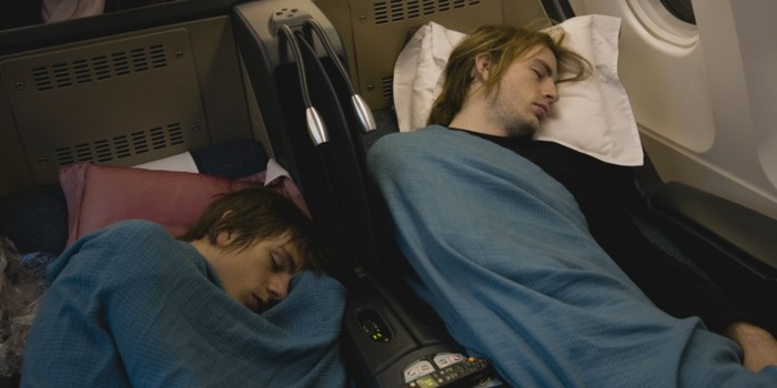 Two young men sleeping in airplane
