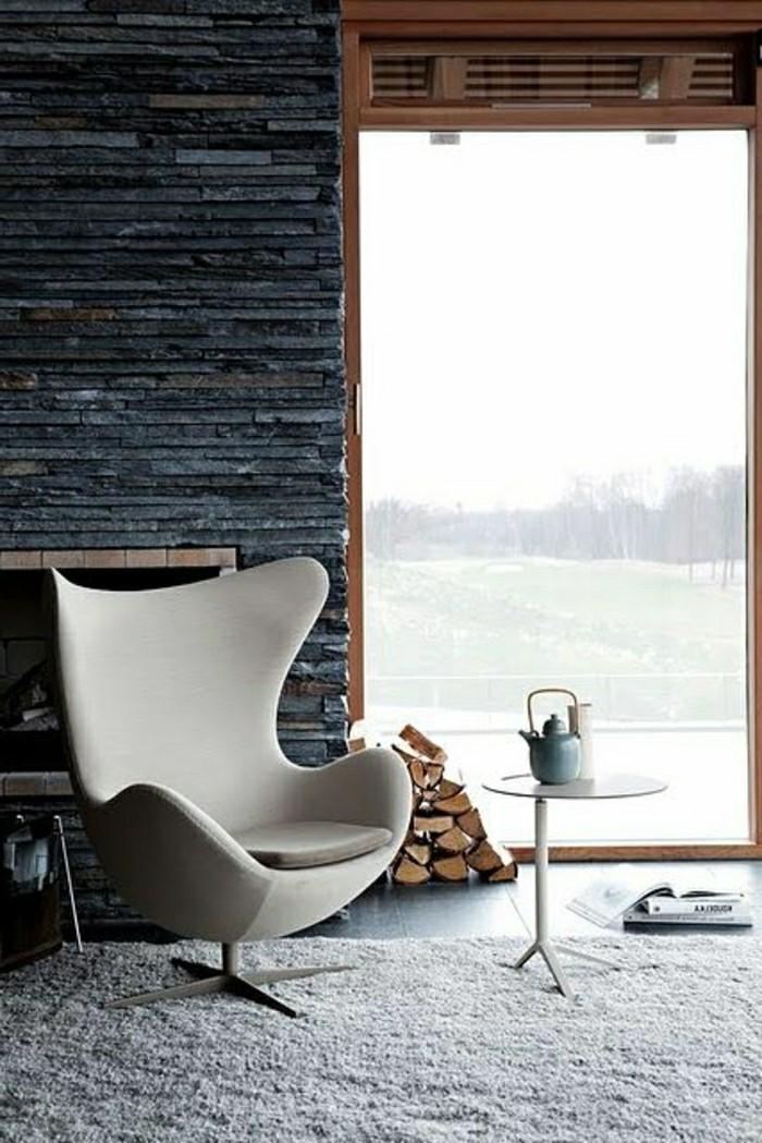 pierres-de-parement-gris-tapis-beige-chaise-beige-mur-en-pierres-gris-cheminée-d-interieur-resized