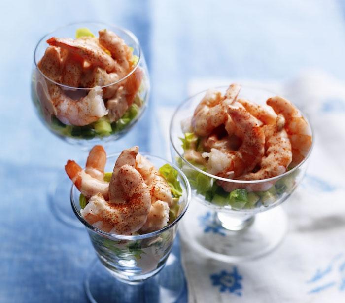 crevettes dans un verre servies sur un canapé d avocat coupé en dés, amuse bouche froid et raffiné