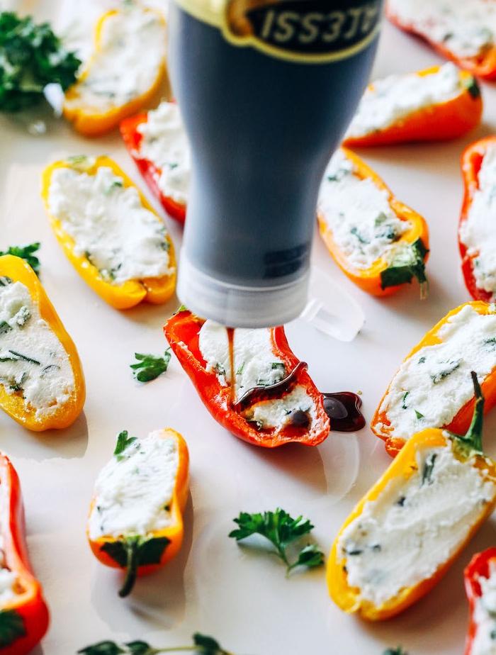 amuse bouche froid réalisé avec des poivrons crudités farcis de fromag à la crème aux herbes avec sauce barbecue