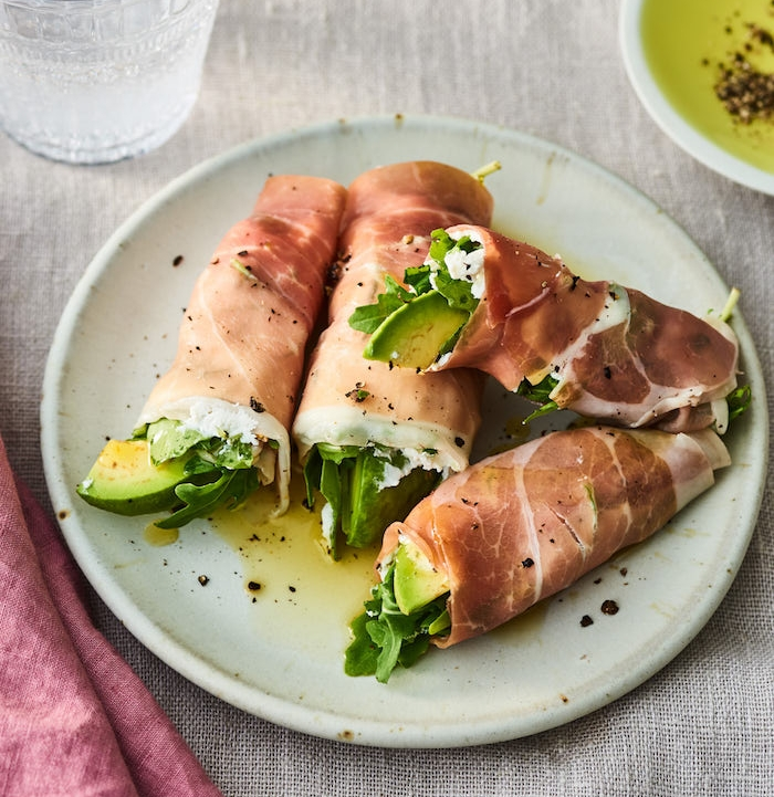 exemple de rouleaux de prosciutto avec du fromage de chèvre, roquette et avocat enveloppées, amuse bouche froid