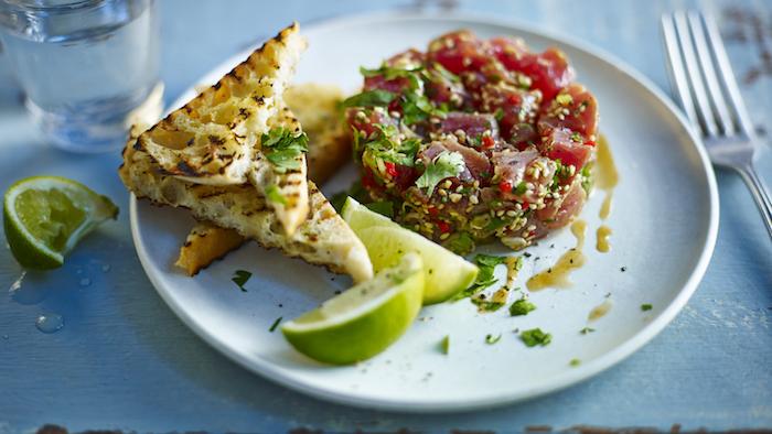 tartare de thon et de sésame avec des herbes fraiches servi avec des toast et des tranches de citron, amuse bouche froid