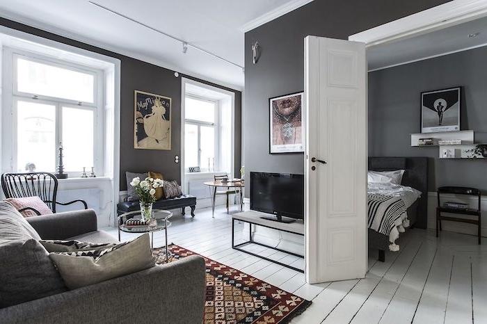deco studio gris et blanc, peinture murale grise, parquet blanchi, canapé gris, lit gris et linge de lit noir et blanc, tapis coloré