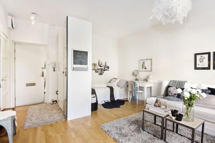aménagement studio avec parquet bois clair, coin couchage gris et blanc avec lit et coiffeuse, canapé blanc, tables gigognes