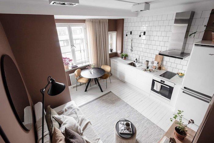 carrelage blanc dans petite kitchenette studio blanche, aspirateur inox, coin repas avec table ronde noire, canapé blanc et coussins couleurs neutre, mur couleur lie de vin