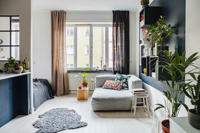 idée comment aménager un studio aux murs blancs, avec coin sejour en petit canapé gris, aprquet bois clair, ilot central bleu marine