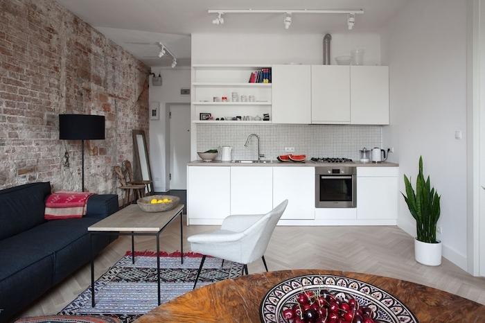 idée déco studio avec mur de briques, cuisine blanche avec carrelage blanc, parquet clair, canapé gris foncé, table bis ronde