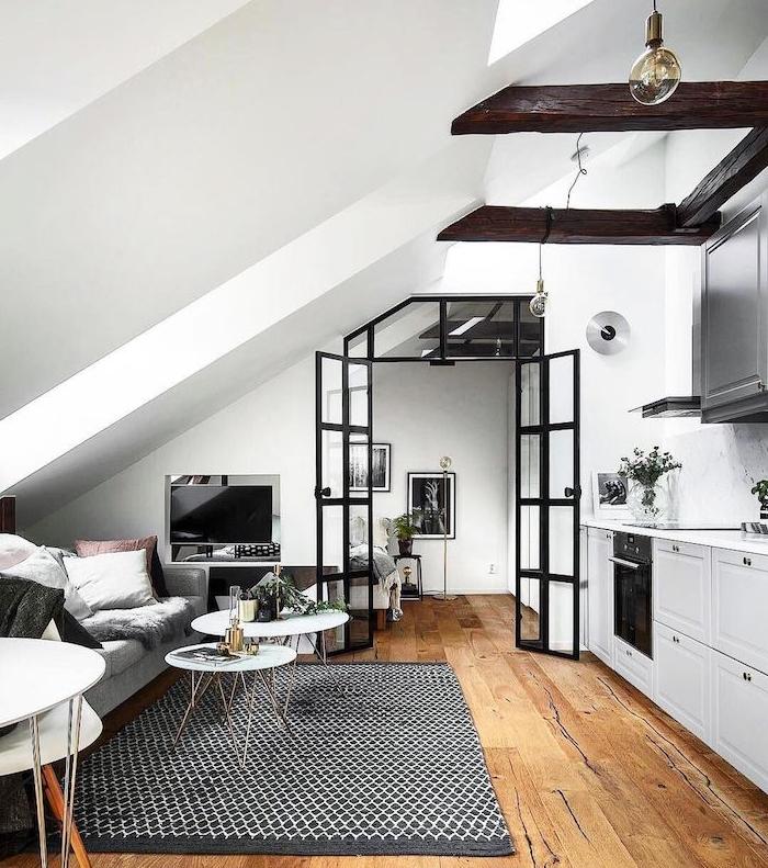 poutres apparentes dans une cuisine blanche ouverte sur salon gris, marron et blanc, tapis noir et blanc, aménagement petit studio style scandinave