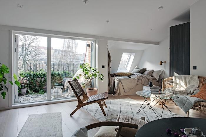 aménager studio dans garage, idée lit sous pente abec linge gris et blanc, canapé et chaise tressée, tapis blanc sur parquet bois clair