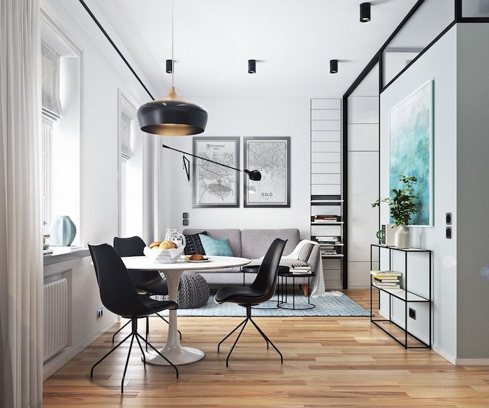 deco salon salle à manger dans studio nordique, coin repas en table blanche ronde et chaises noires, canapé gris et table basse noire en metal