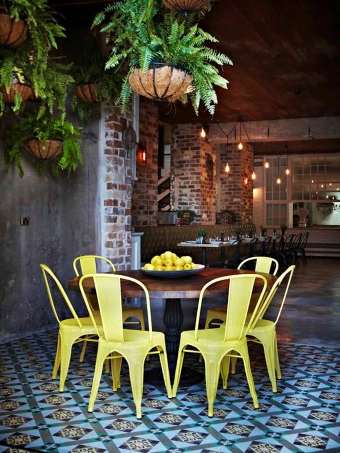 chaises-en-fer-jaunes-sol-en-dalles-colorés-mur-en-briques-table-en-bois-massif-foncé