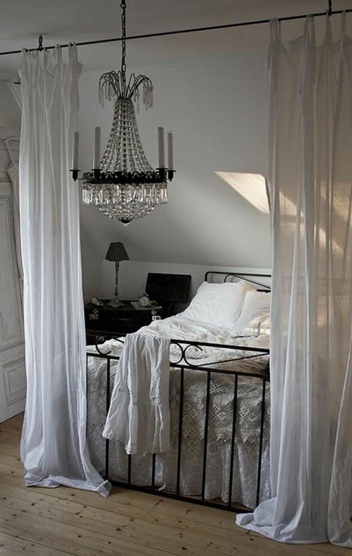 chambre-a-coucher-lit-en-fer-forgé-noir-sol-en-parquet-clair-lustre-en-crystal-chambre-a-coucher