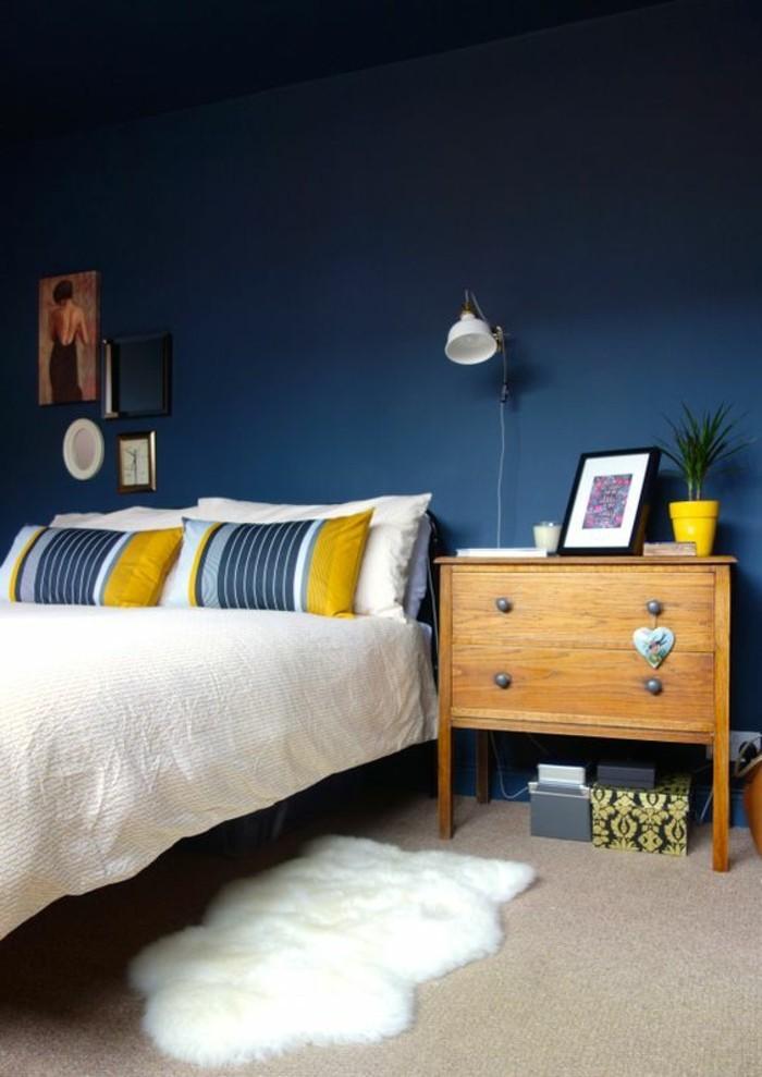 chambre-a-coucher-mur-en-bleu-foncé-table-d-appoint-en-bois-clair-tapis-en-fourrure-blanc