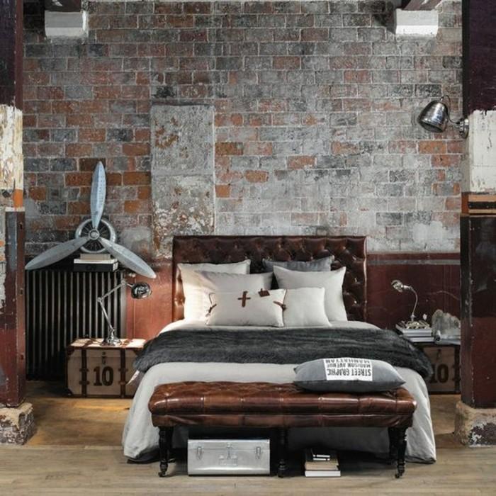 chambre-a-coucher-tete-de-lit-capitonnée-simili-cuir-marron-sol-en-parquet-clair-mur-en-briques