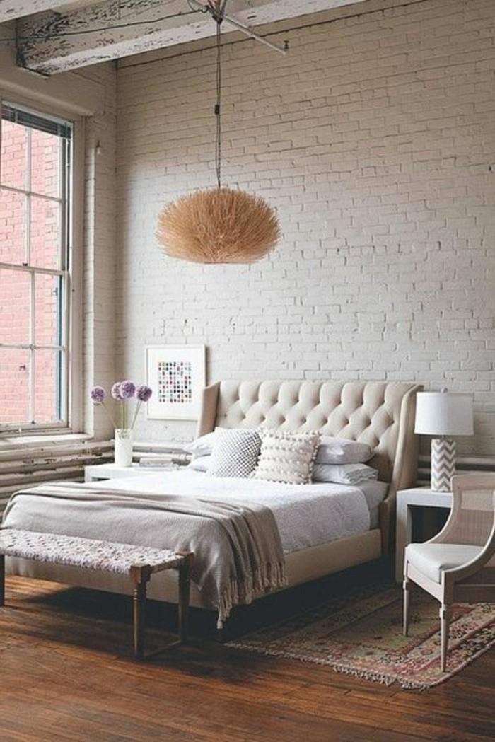 chambre-de-lixe-avec-lit-en-cuir-beige-sol-en-bois-lustre-suspendu-chambre-a-coucher-briques-beiges