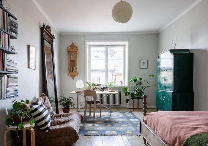 exemple d aménagement studio avec canapé marron par sol, lit en bois sur parquet bois clair, armoire verte, grand miroir, bureau
