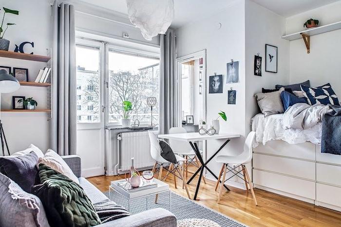 petit lit avec tiroir intégré et linge de lit gris, blanc et bleu marine, canapé gris décoré de coussins colorés ouverture sur coin repas blanc aux meubles scandinaves