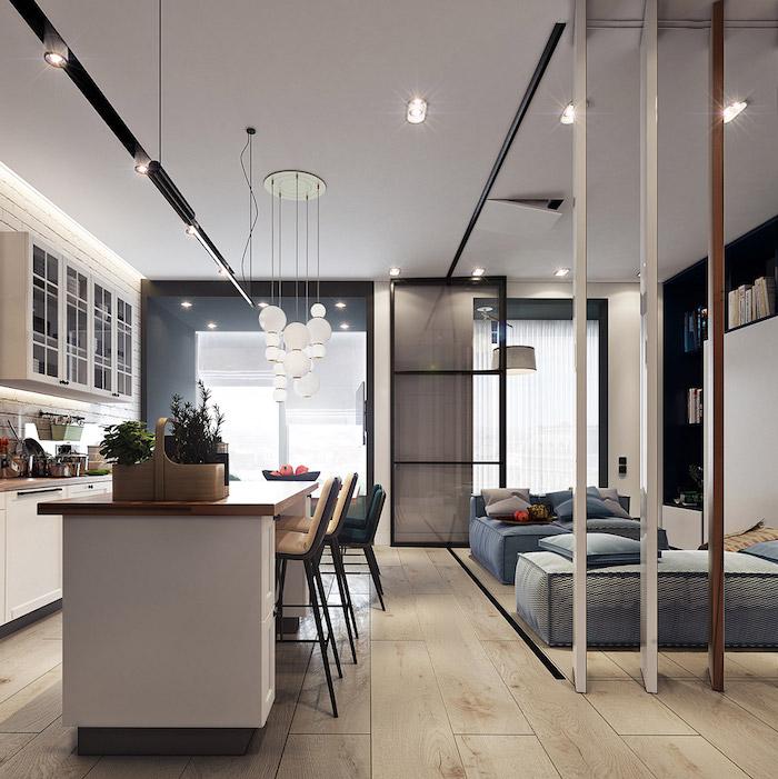 ilot central et cuisine toute blanche ouverte sur coin couchage et salon, suspension blanche et parquet bois clair