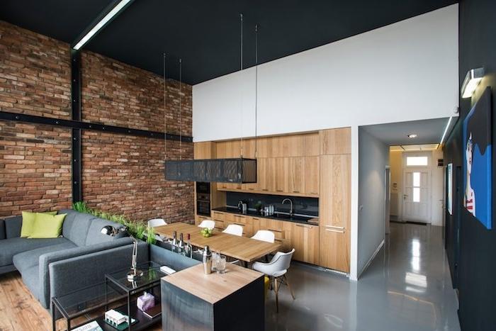 deco loft industriel avec mur de briques, cuisine noire et bois ouverte sur salle à manger avec table bois et chaises scandinaves, coin sejour avec canapé gris