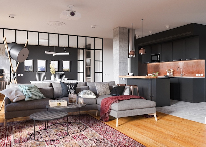 cuisine gris anthracite avec credence effet rouille ouverte sur salon avec canapé gris, tables basses grises, verrière salle à manger blanche