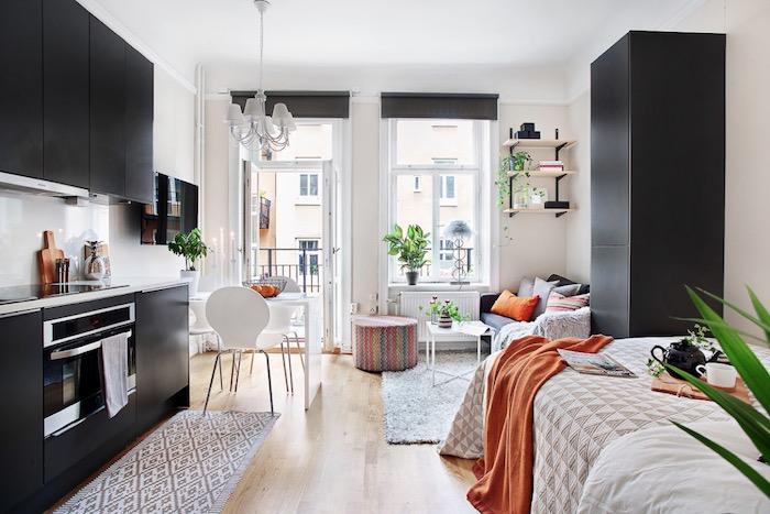 cuisine noire avec credence blanche ouverte sur salle à manger, salon, chambre à coucher, idee interieur deco scandinave aux accents orange