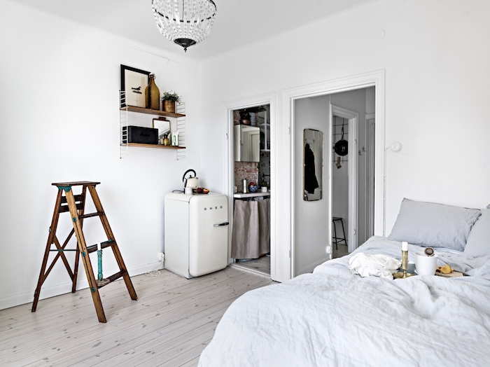 murs blancs дdans une chambre à coucher gris et blanc semi ouverte sur cuisine, deco murale etagere bois et metal, amenagement petit espace