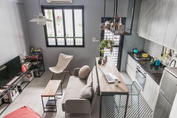 cuisine bois gris ouverte sur salle à manger en bar ilot et salon avec canapé gris, etagere meubl tv noire, murs gris