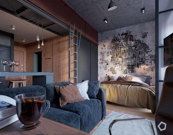 cuisine bois et gris ouverte sur salon avec canapé gris anthracite, chambre avec lit et tete de lit papier peint original, decoration loft industriel