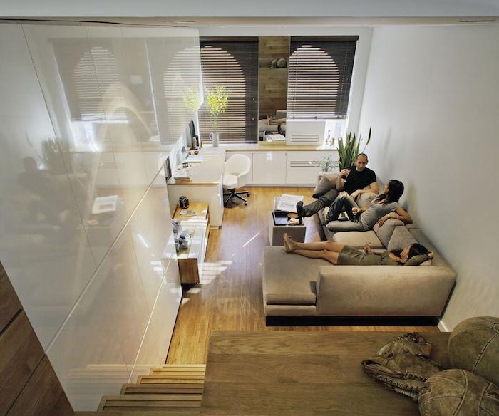cuisine ouverte sur petit coin sejour avec canapé gris, cuisine blanche, parquet bois clair, lit mezzanine en hauteur