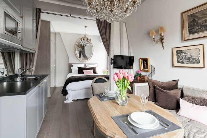 deco vintage aménagement studio 20 m2 avec canapé gris, table bois, cuisine blanche et grise, chambre à coucher gris et blanc