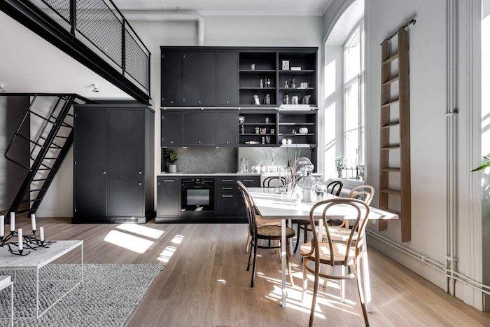 decoration cuisine noire ouverte sur salle à manger avec table blanche et chaises de bois, parquet bois clair, coin sejour style scandinave