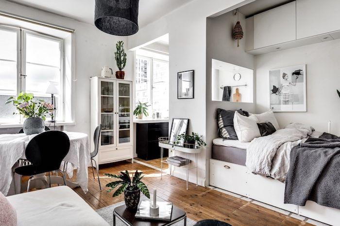 aménager un studio style scandinave avec lit gris et blanc, parquet bois, table à manger entourée de chaises noires, murs blancs