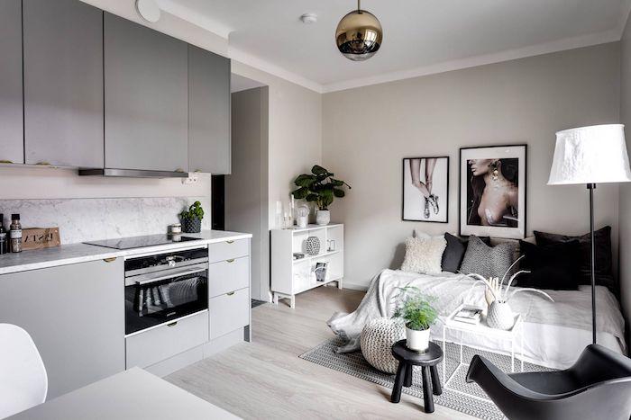 meuble haut gris et meuble bas gris, lit blanc décoré de coussins blanc, gris et noirs, murs gris perles, parquet gris clair