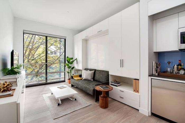 cuisine blanche et inox ouverte sur coin salon en gris et blanc, murs blancs, grandes portes vitrées, parquet bois clair, meuble tv blanc