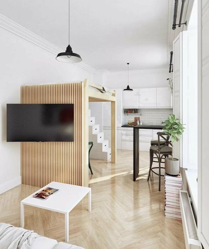 lit surelevé sur une estrade de bois dans un studio blanc et bois avec cuisine kitchenette studio blanche
