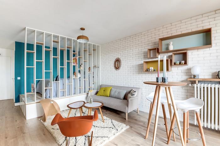 aménagement petit appartement avec lit sur estrade isolé d une étagère, murs de briques blanches, canapé gris, tables basses bois et blanc, chaise à bascule orange, table bar bois entourée de tabourets bois et blanc