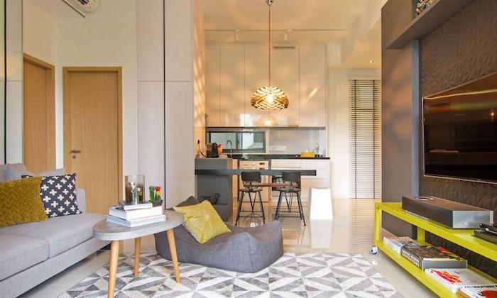 kitchenette studio blanche avec bar gris entourée de tabourets de bar grises, cuisine ouverte sur salon avec canapé gris, table gris et bois, meuble tv jaune
