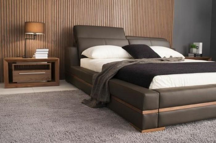 lit-en-cuir-marron-tapis-gris-mur-en-lambris-en-bois-chambre-a-coucher-stylé-lit-en-cuir
