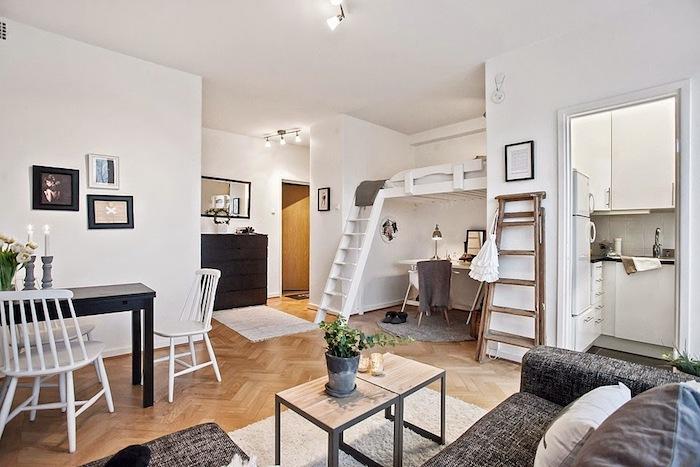 coin bureau sous lit surélevé, kitchette semi ouverte sur salon avec canapé gris anthracite, tables basses gris et bois, table salle à manger noire et chaises blanches