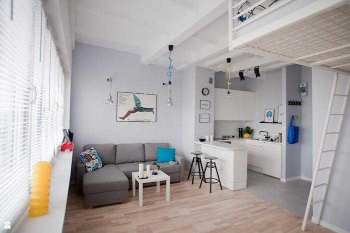 kitchenette d angle couleur blanche dans studio aux murs gris, cuisine ouverte sur salon avec canapé gris et table basse blanche, parquet bois clair, lit mezzanine en hauteur