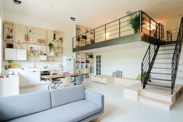 idée amenagement petit appartement avec cuisine d angle blanche, rangement cuisine panneau perforé, sol blanc et canapé gris