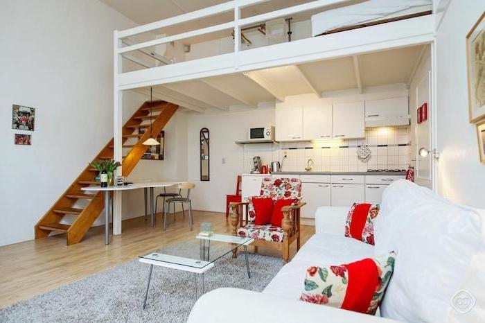 lit mezzanine blanc au dessus d une cuisine kitchenette blanche ouverte sur salon avec canapé blanc et table en verre sur tapis gris sur parquet bois clair