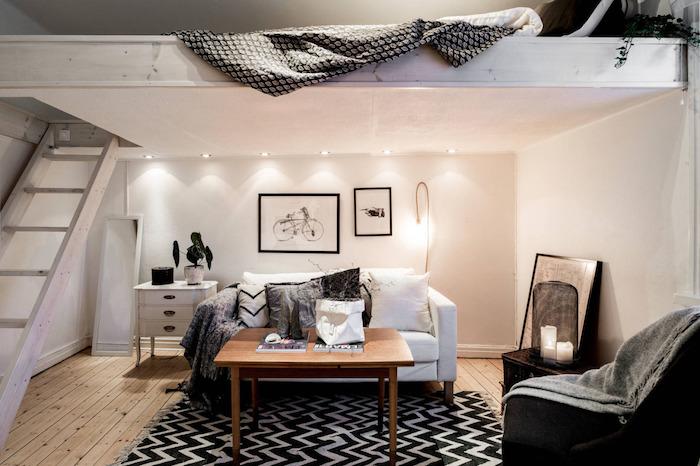 idée déco lit surelevé mezzanine avec coin sejour en dessous avec canapé blanc, table bois sur tapis chevron noir et blanc, décoration appartement étudiant