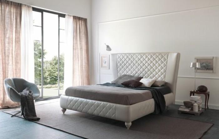 lit-roche-bobois-en-cuir-beige-chambre-a-coucher-avec-grandes-fenetres-et-tapis-beige