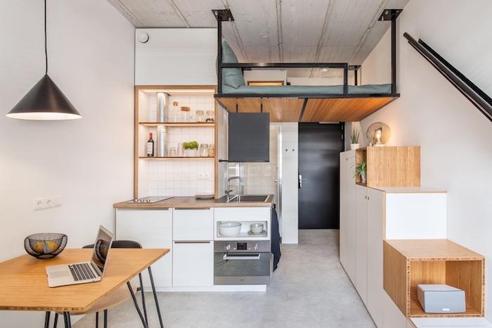 kitchenette studio bois et blanc avec lit mezzanine en dessus avec matelas et coussin gris, sol effet béton, table bois et metal