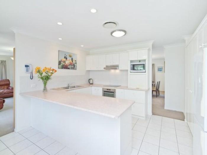 magnifque-cuisine-blanche-avec-bar-de-cuisine-en-bois-sol-en-carrelage-blanc