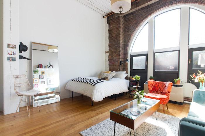 mur de briques avec grande baie vitrée, lit avec draps blancs dans un salon avec canapé bleu et table en bois et verre, tapis gris sur parquet bois
